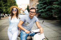 Young beautiful couple riding on motorbike city street summer europe vacation. Young beautiful couple riding on motorbike city street, summer europe vacation stock photography