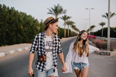 Young beautiful couple on romantic outdoor date enjoys freedom and warm summer evening in south city. Boy in trendy. Checkered shirt and girl in vintage white stock image