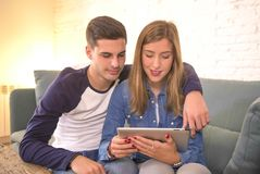 Young beautiful couple 20s using digital tablet pad computer sitting at home couch living room shopping on line choosing items on. Internet smiling happy and Royalty Free Stock Images