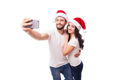 Young beautiful couple in Santa hats in love taking romantic self portrait. Christmas young beautiful couple in Santa hats in love taking romantic self portrait Royalty Free Stock Images