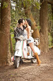 Young beautiful couple with scooter along dirt road. Young beautiful couple kissing with scooter along dirt road Stock Images