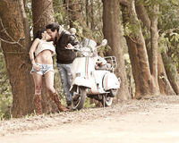 Young beautiful couple with scooter along dirt road Royalty Free Stock Images