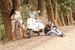 Young beautiful couple with scooter along dirt road Stock Images