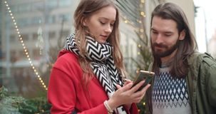 Young beautiful couple share memories and pictures on social media with online mobile app. Attractive couple spending day together in a city. Concept of royalty free stock photos