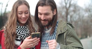 Young beautiful couple share memories and pictures on social media with online mobile app. Attractive couple spending day together in a city. Concept of royalty free stock images