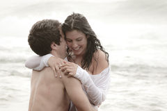 Young beautiful couple sharing an intimate moment. In the surf Stock Photography