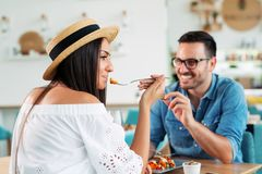 Happy couple with friends eating at restaurant. - Image royalty free stock photo