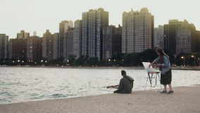 Young Beautiful couple on the shore of Michigan lake, Chicago, America. Woman draw, man play guitar. stock video footage