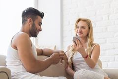 Young Beautiful Couple Sit On Coach Near Window, Using Cell Smart Phone Happy Smile Hispanic Man Woman. Young Beautiful Couple Sit On Coach Near Big Window royalty free stock photography