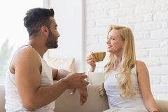 Young Beautiful Couple Sit On Coach Near Window, Drink Morning Coffee Cup, Happy Smile Hispanic Man And Woman. Lovers royalty free stock photography