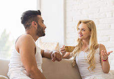 Young Beautiful Couple Sit On Sofa Talking, Hispanic Man Woman Drink Morning Coffee Cup Stock Photo