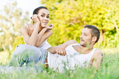 Young beautiful couple sits on Royalty Free Stock Photos