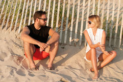 Young beautiful couple sitting on beach enjoy sunset and romantic atmosphere. Stock Photography