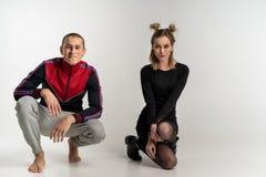 Young beautiful couple sitting on the floor, studio portrait stock photography