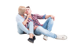 Young and beautiful couple sitting happy on white floor Royalty Free Stock Photos