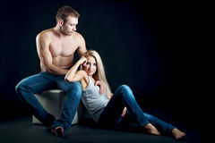 Young beautiful couple sitting. isolated shot. Portrait of a young couple sitting. erotic love picture. couple dressed in a casual style, blue jeans. a man's Royalty Free Stock Photo