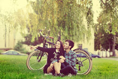Young beautiful couple sitting near a vintage bike and pointing Stock Images