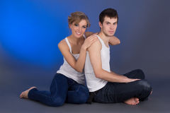 Young beautiful couple sitting over blue Stock Photos