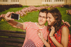 Young beautiful couple sitting on the park bench and taking self portrait with smartphone on beautiful sunny day.  Stock Photo