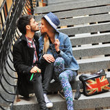 Young beautiful couple sitting on the stairs and having fun toge Royalty Free Stock Photo