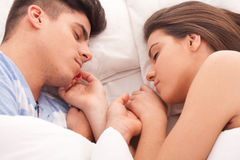 Young beautiful couple sleeping. Lovely couple sleeping together in bed stock photos