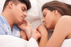 Young beautiful couple sleeping together in bed Royalty Free Stock Images