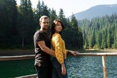 Young beautiful couple smiling, embracing, lake and mountains background. Young beautiful couple smiling, looking at camera, embracing, lake and mountains Stock Photo