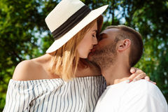 Young beautiful couple smiling, kissing, embracing, walking in park. Royalty Free Stock Photo