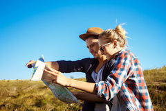 Young beautiful couple smiling, looking for route on map. Stock Images