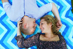 Young beautiful couple smiling and lying on the blanket on the grass in the park. Royalty Free Stock Photo