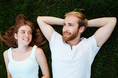 Young beautiful couple smiling, lying on grass in park. Shot from above. Stock Photos