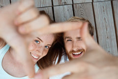 Young beautiful couple smiling, lying on wooden boards making frame with hands. Focus at faces. Royalty Free Stock Photography