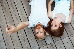 Young beautiful couple smiling, lying on wooden boards. Shot from above. Stock Image