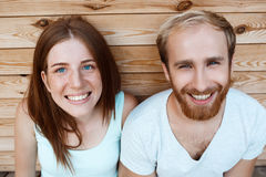 Young beautiful couple smiling, posing over wooden boards background. Stock Photo