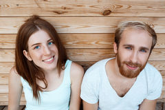 Young beautiful couple smiling, posing over wooden boards background. Royalty Free Stock Photo