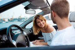 Young beautiful couple smiling, sitting in car near sea. Royalty Free Stock Photo