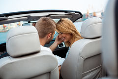 Young beautiful couple smiling, sitting in car near sea. Royalty Free Stock Images