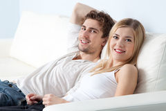 Young beautiful couple on a sofa at home Royalty Free Stock Image