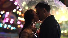 Young beautiful couple spending time together, kissing on date in amusement park at night. Rainy weather, autumn. Lovers. Standing under umbrella. Illuminated stock footage
