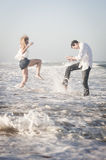 Young beautiful couple splashing in the surf at the beach Royalty Free Stock Image