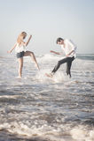 Young beautiful couple splashing in the surf at the beach Royalty Free Stock Photography