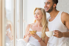 Young Beautiful Couple Stand Near Big Window, Drink Morning Coffee Cup, Happy Smile Hispanic Man And Woman Royalty Free Stock Photography