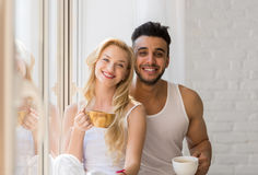 Young Beautiful Couple Stand Near Big Window, Drink Morning Coffee Cup, Happy Smile Hispanic Man Woman Stock Photo