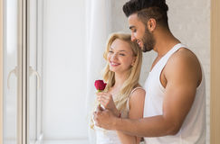 Young Beautiful Couple Stand Near Big Window, Hispanic Man Give Woman Red Rose Stock Photo