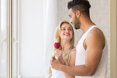 Young Beautiful Couple Stand Near Big Window, Hispanic Man Give Woman Red Rose Royalty Free Stock Photos