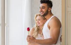 Young Beautiful Couple Stand Near Big Window, Hispanic Man Give Woman Red Rose Stock Photography