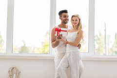 Young Beautiful Couple Stand Near Window Embrace Hold Present Envelope, Happy Smile Hispanic Man And Woman Stock Photo
