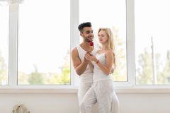 Young Beautiful Couple Stand Near Window Embrace Hold Red Rose, Happy Smile Hispanic Man And Woman Royalty Free Stock Images