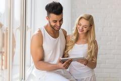 Young Beautiful Couple Stand Near Window, Hispanic Man Woman Using Tablet Computer Stock Photos