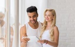 Young Beautiful Couple Stand Near Window, Hispanic Man Woman Using Tablet Computer Stock Photography